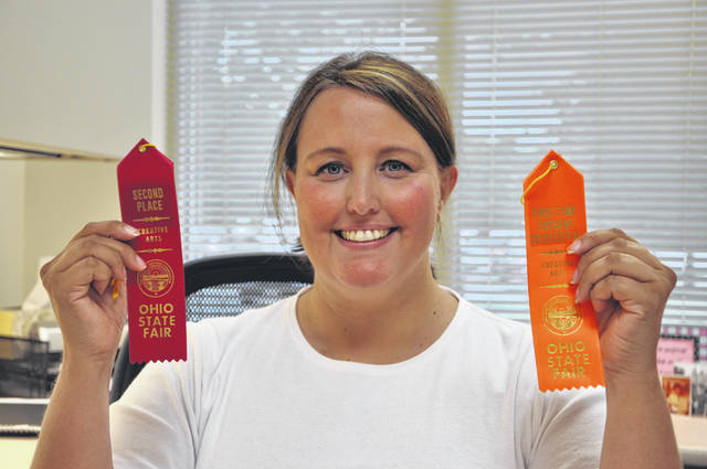 "Angela Riley holds up her ribbon for second place and the award for best newcomer that she received after competing in the ""Egg-citing and Devilishly Good"" competition at the Ohio State Fair."