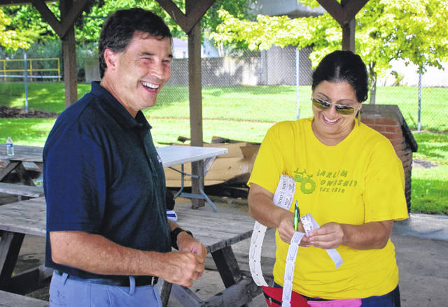 Once the heavy downpour of rain stopped, state Sen. Troy Balderson walked around the Harlem Township Days Festival Saturday looking at old tractors and steam engines. Several eventgoers stopped to shake hands with the Republican who has claimed himself the unofficial winner of the Aug. 7 special election for Ohio's 12th Congressional District seat. Pictured is Michelle Solomon, a member of Harlem Township Heritage, asking Balderson to purchase a raffle ticket to support the local organization.