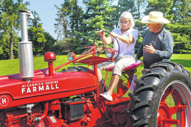 "When ""Virginia"" was built, it was for hard labor on a farm, but according to The Barn Venue Manager Connie Hoffman, the 1941 Farmall Tractor will have a new purpose at the Meeker Homestead Museum as a photo prop for weddings, pulling hayrides, and hauling things around on the museum property. Hoffman, sitting in the driver seat of the old tractor, receives a driving lesson from Greg Nobis. Nobis and his wife, Suzan, donated ""Virginia"" Tuesday to the Delaware County Historical Society."