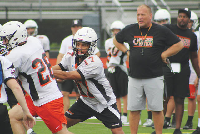 Blake Eiland (17) runs a play under the watchful eye of coach Scott Wetzel during a practice earlier this summer.