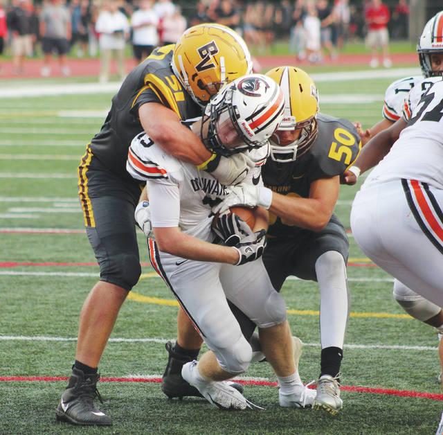 Buckeye Valley's Wyatt McGraw, left, and Lathan McGraw combine to take down Delaware Hayes' Luke Jackson as he powers toward the goal line during the first half of Friday's season opener at OWU's Selby Stadium.