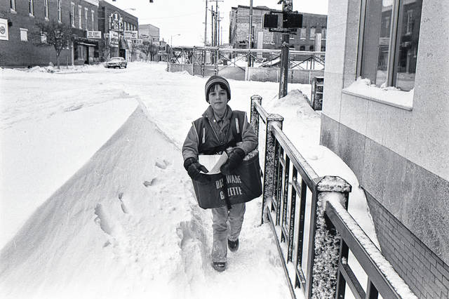 The Great Blizzard of 1978 didn't stop Chris Brien, who was 11 years old at the time, from delivering The Delaware Gazette. Brien was one of about 44 carries that year who delivered papers to city residents. Brien is pictured walking west on West Winter Street between a 4-foot snow drift and the Delaware County Bank, which is now First Commonwealth Bank. In the background, construction had just started on what is now the PNC Bank building on North Sandusky Street. The building also houses The Gazette office. The photo was taken on Friday, Jan. 27, 1978, by Rex Welker.