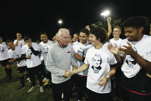 Ohio Wesleyan coach Jay Martin celebrates with his players after securing his 700th-career win Saturday night. He's the first NCAA men's soccer coach in any division to reach the 700-win mark