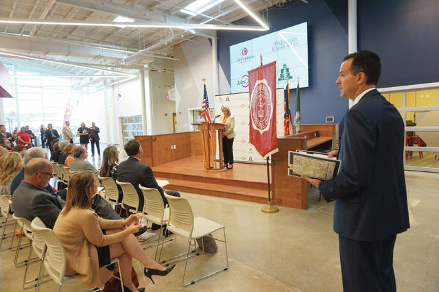 Otterbein President John Comerford (right, standing) looks on as Corrine Burger of JPMorgan Chase announces a fintech partnership with the university.