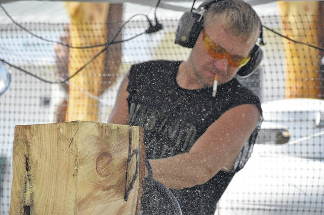 Chainsaw artist Tim Crager saws away at a the top of a bench Wednesday afternoon at the Delaware County Fairgrounds. Crager said he's been chainsaw carving for about five years, and he added some pieces take him as long as 35 hours to carve.