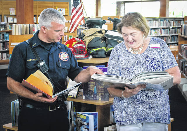 Capt. A. J. Miller, Orange Township Fire Department, looks through some of the books that make up library associate Cindi Bardash's display dedicated to the first responders of 9/11. The tribute is on display at the Orange Branch of the Delaware County District Library, 7171 Gooding Blvd., Delaware.