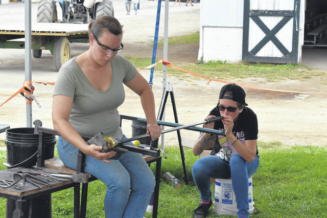 Glass artist Michelle Pennington spins and shapes glass while fellow artist Alexa Adamczyk blows into the other end of the pipe. The pair did not know each other before this summer, but both signed up to perform at 10 fairs this summer on behalf of Mobile Glass Studios.