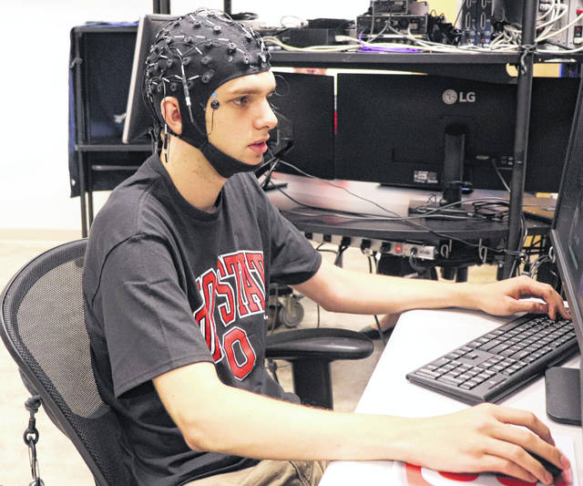 Lucas Lumbra plays a video game while wearing an electroencephalography, or EEG, helmet. It allows researchers at The Ohio State University Wexner Medical Center to examine brain activity and identify the unique cognitive attributes of esports athletes.