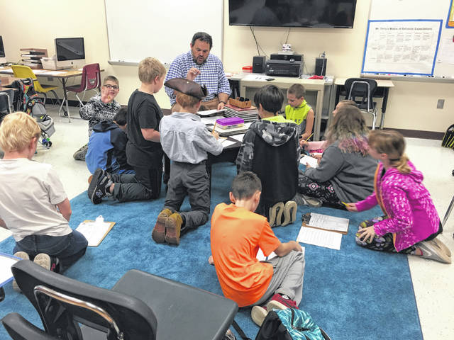 Smith Elementary School teacher P.J. Terry walks a group of 14 students through creating their Dungeons and Dragons characters Thursday morning before school. Terry said he hopes the game teaches students about how to creatively solve problems and how their actions have consequences.