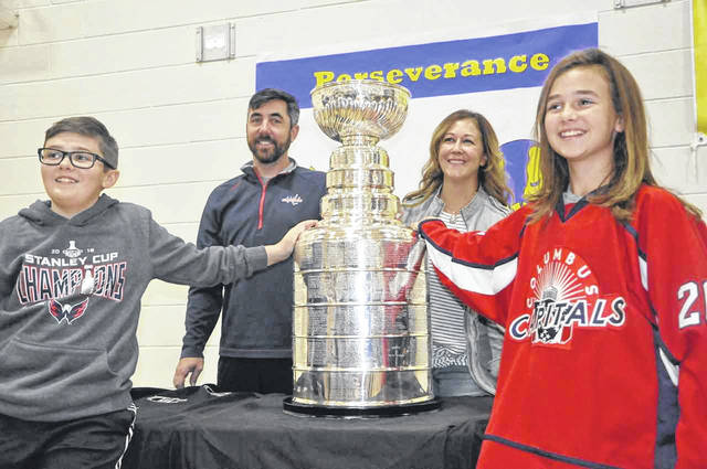 Washington Capitals Director of Hockey Operations Kris Wagner, along with his wife, Jenn, and children, Ty and Addie, pose with the Stanley Cup during its stop at Shanahan Middle School on Friday.