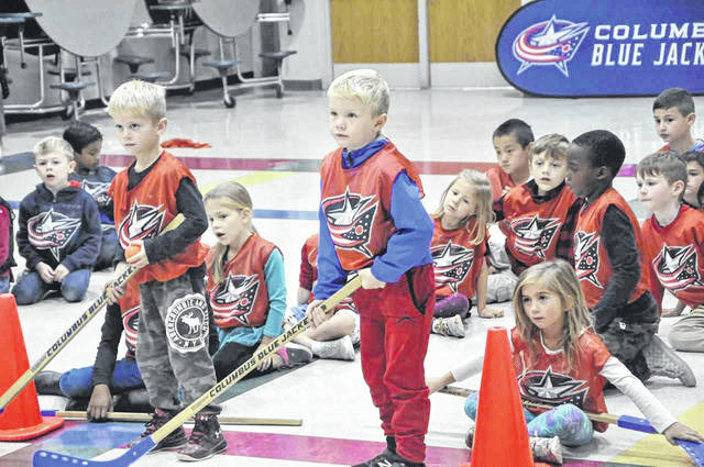 Oak Creek Elementary first-graders Tatum Weaver (left) and Carson Radebaugh (right) listen to instructions before beginning a passing drill.