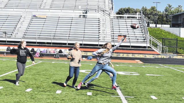 A group of students on one powderpuff team attempt to catch a pass Friday. Coaches and players from the Hayes football team were on hand Friday to give tips to the powderpuff teams and to teach them plays and strategies.