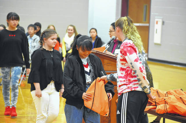 A Dempsey Middle School student gives a gift bag to a visiting student from Sakata, Japan, who will be staying with her for the next four days. The students were paired with their hosts Friday afternoon during a welcome assembly at Dempsey.
