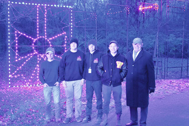 "Recreation Unlimited CEO and Executive Director Paul Huttlin poses with a group of seniors from the welding program at the DACC Tuesday evening after the display was lit up. Huttlin said the display was ""fantastic,"" and he thanked the students for their work on the project."