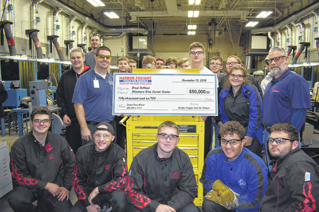 Bradley DeMent, left of check, poses with his students in the Delaware Area Career Center welding lab Thursday after being given a personalized tool cart and a check for $50,000 by Gerald McLarnon, right, a representative from Harbor Freight Tools For Schools.