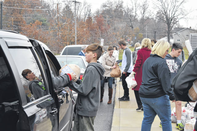 Hayes High School students and community members work to load food into vehicles Tuesday morning. The donated food included a turkey, rolls, stuffing and sides. Drivers would pull up and tell the students how many people they had to feed and the students would load the appropriate amount of food into the vehicles.