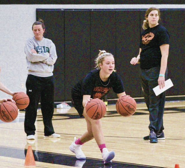 Delaware Hayes' Piper Adkins (center), one of two captains on the girls basketball team, runs through a drill in practice as assistant coaches Chelsea Burden (left) and Lydia Hyburg (right) look on.