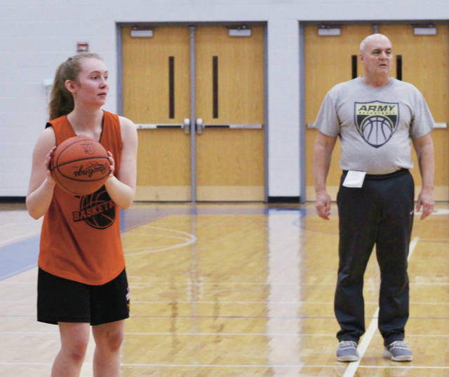 Olentangy Orange senior Lauren Perrone (right) looks for an open teammate as coach Bob Scott looks on during a practice earlier this month.