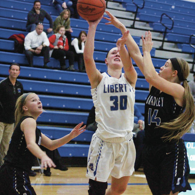 Olentangy Liberty's Teegan Pifher (30) puts up a shot over Hilliard Bradley's Jaiden Bryant (14) during the first half of Tuesday's non-league showdown in Powell.