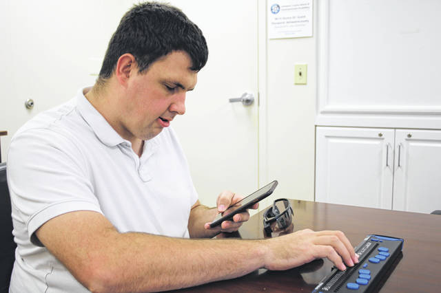During a recent visit to the Delaware County Board of Developmental Disabilities office on Columbus Pike in Lewis Center, Chris demonstrates how his new smart glasses and braille display works.