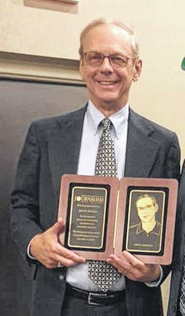 Liberty Township resident John K. Hartman is pictured with his Central Michigan University Journalism Hall of Fame plaque.
