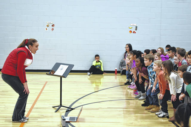 Woodward Music Teacher Mandi Rederstorff leads first-graders in a dance Wednesday afternoon during a dress rehearsal for Woodward's annual holiday program. The free concert will be held today at 7 p.m. at the Willis Education Center.
