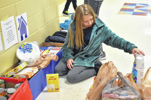 Brynna Pauley, a fifth-grader and member of the Tar Heel house, counts donations Thursday afternoon at Schultz Elementary School. Each house at Schultz had a specific list of items they were supposed to donate, and the donations will be tallied on Dec. 14. The winning team get a pizza party with athletes from Hayes High School.