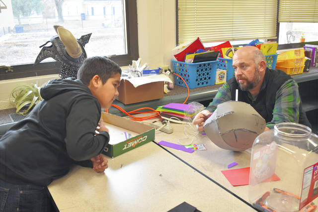 Makers Club student Ignacio Rizo discusses the foam helmet he is working on with Woodward fifth-grade teacher Robert Sexton Thursday afternoon during the weekly Makers Club meeting. Sexton said the goal of the club is to teach kids how to build things with their hands and gain skills.