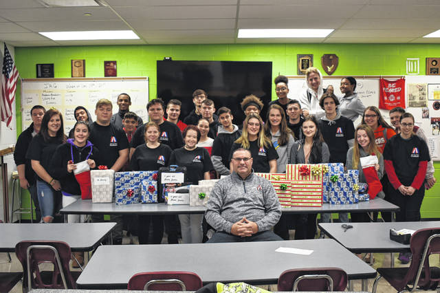 Juniors and seniors in the JAG class at Hayes pose with the gifts they bought and wrapped for a local family. Instructor Mark Thomas, center, said the students bought about $600 in gifts for a local woman and her two sons. Thomas said the money for the project came from JAG funds and money that students kicked in.