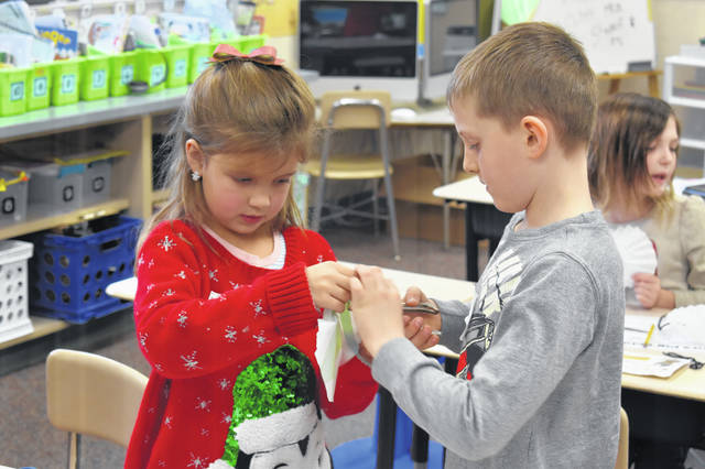 Piper Mustard, left, and Gage Boylan, right, use a hole puncher to put a hole in their parachute so they can attach it to another part of their design. The goal of the project was to make sure Santa landed safely if his sleigh broke down.