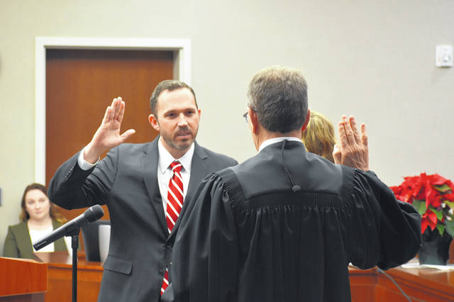 James P. Schuck is sworn in as a judge of the general division of the Delaware County Common Pleas Court by retiring Judge Everett H. Krueger Friday afternoon.