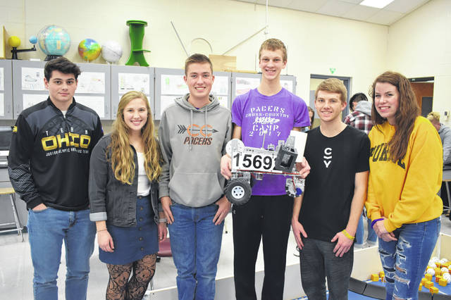 Six of the members of the robotics team pose with their robot Friday. From left to right are Jacob McCloskey, Megan Fanok, Dominic Hupp, Eric Puthoff, Jonah Wallace and Sydney Krewson. Matt Thompson is also a member of the team, but he is not pictured.