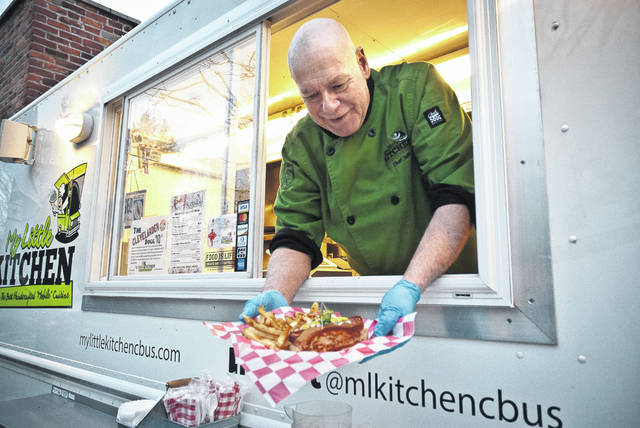 """Voted one of Central Ohio's top three best food trucks, My Little Kitchen Mobile Cuisine can be found sitting alongside the Staas Brewing Company on the corner of West Winter and North Franklin streets on any given Thursday evening. Chef Jeff Snyder said his fresh, non-GMO food is """"from the farm to the truck."""" Snyder is holding a plate of hot dogs, made by him from an old family recipe, and fries that many customers rave about."""
