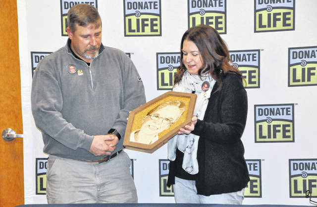 Chris and Marcia Wasielewski look at a floragraph of their late son, Adam, during an event held Tuesday at the Lifeline of Ohio office in Columbus. To honor Adam, a cornea and tissue donor, the floragraph will be part of the Donate Life float that will appear in the upcoming Tournament of Roses Parade in Pasadena, California.