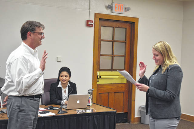 Delaware City Schools Treasurer Melissa Lee, right, swears in Matt Weller, left, as board vice president Monday night.
