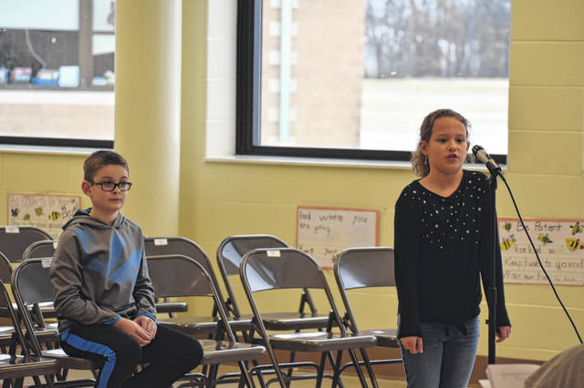 "Fourth-grade student Leighton Sessor spells a word Thursday afternoon during the final rounds of the Schultz Elementary School spelling bee. Sessor said she felt ""really good"" about winning the competition after being last year's runner-up. This year's runner-up, Mick Wiener (left), said he was surprised he made it that far."