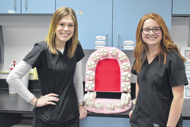 DACC Dental Assisting students Abby Baker, left, and Allie Holdcroft, right, pose next to a model of a mouth they made to teach elementary school students how to effectively floss. The pair said they've done at least 10 presentations about dental hygiene at elementary schools, and they want to raise awareness of how important oral health is.