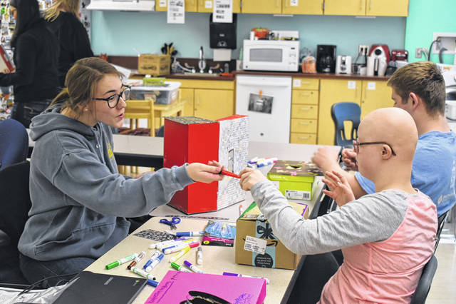 Senior Mackenzie Collett, left, works with junior Nathalie Young to decorate a Valentine's Day box Friday during the Peer Mentoring Club at Hayes High School. Collett said she's glad attendance in the club has jumped this year, which she attributed to positive word of mouth.