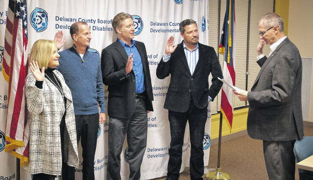 Newly appointed Delaware County Board of Developmental Disabilities members were sworn in Thursday evening by Delaware Commissioner Gary Merrell. The photo shows, from left to right, Dana Lehman, Stephen Finney, Theodore Klecker, and Louis Borowicz being sworn in by Merrell.