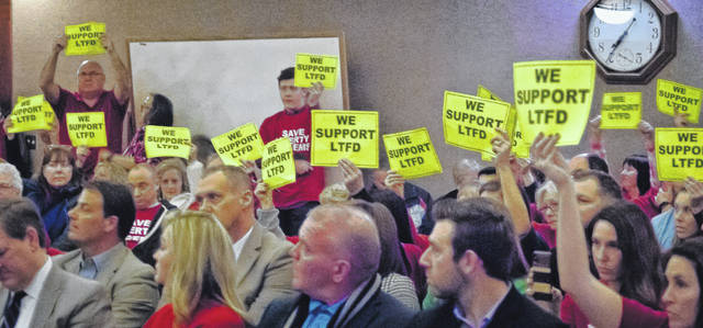 "Before the Liberty Township Board of Trustees meeting began Tuesday night, the grassroots organization ""Save Our Services,"" who oppose handing over the township's fire-based EMS model to Delaware County, handed out signs to residents that said ""We support LTFD"" on one side and ""Please Be Quiet"" on the other."
