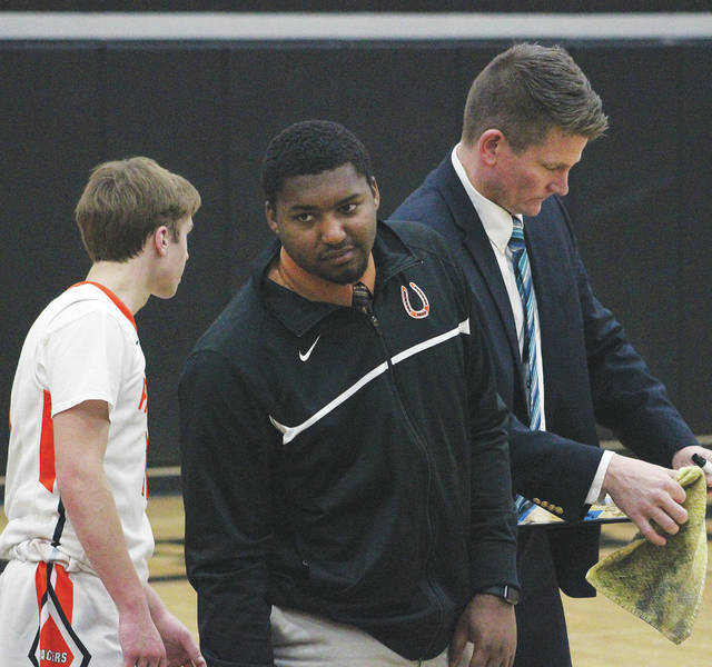 Delaware Hayes assistant coach Keith Butts, center, listens to Ryan Smudz, left, as head coach Jordan Blackburn draws up a play during a game earlier this season.