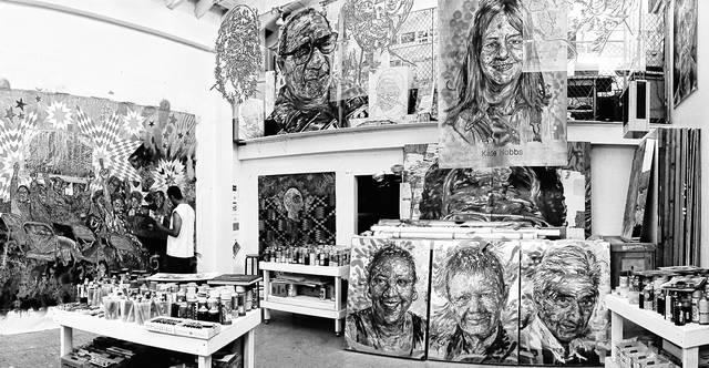 Artist Brett Cook works in his studio in this black and white photography. He will meet with the community this week to continue planning for a downtown Delaware mural project.
