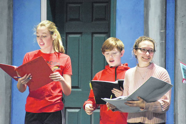 Meredith Keller (Mary Poppins) rehearses with Elijah Belcher (Michael Banks) and Madeline Thompson (Jane Banks) Wednesday after school in the auditorium at Hayes High School. Scenes were being blocked this week, meaning the cast practiced their lines while learning where they should stand and move during the scene.