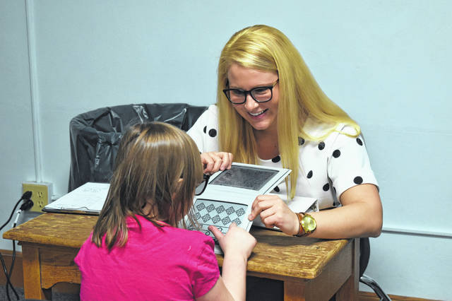 Bowling Green State University pre-optometry student Shelby Gelhaus gives an eye exam to a student from Woodward Elementary School Wednesday afternoon. After the free examinations, students were given a prescription and allowed to choose a frame for their glasses. The glasses are expected to arrive in two weeks.