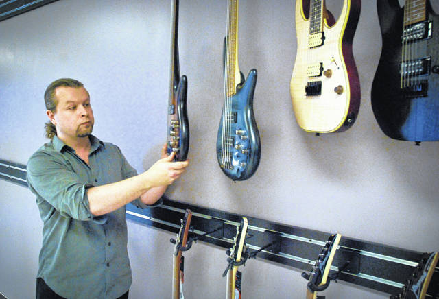 With a March 2 opening date fast approaching, Delaware Music Center owner Adam Furay was glad to see the guitar hooks that were backordered showed up Monday so that he could get some of the 200 guitars he plans to display on the 48-foot wall hung before the store's opening.