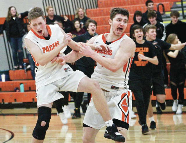 Hayes' Terin Kinsway, right, and Ben Madden celebrate after the Pacers held on for a 56-55 win over Westerville Central in the first round of the Division I district tournament Saturday afternoon in Delaware.