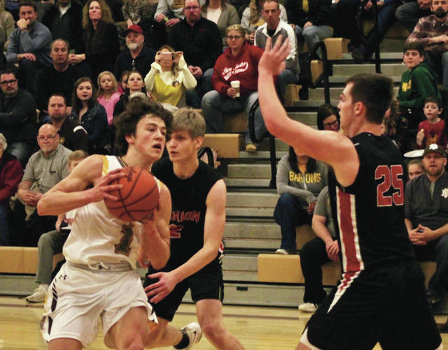 Buckeye Valley freshman Dylan Thompson (1) drives toward the hoop as Marion Harding's Mitch Myers (25) defends in Saturday night's game in Delaware. Thompson scored a game-high 18 to lead the Barons to a 64-23 win in MOAC play.