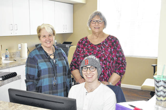 Pictured in the newly-constructed connector building at Turning Point Delaware are Shelter Director Kathy King (left), Turning Point Executive Director Paula Roller (right), and employee Maxwell Aaronson at the reception desk.