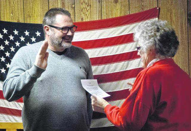 Dorothy Wilcox, Village of Ostrander clerk, right, thought it would be appropriate that Robert Taylor, left, stands in front of the U.S. flag hanging in the village hall to take the oath of office as mayor. Taylor had been serving as the interim mayor since the resignation of Larry Crile, former mayor, on Feb. 11.