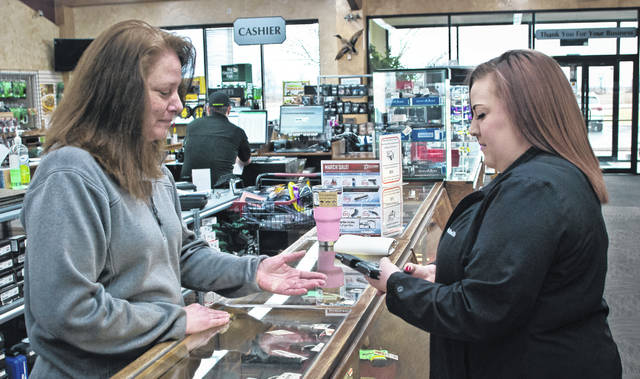 Robin Salvo, left, director of the Black Wing Shooting Center, 3722 Marysville Road, Delaware, helps Danielle Creske, right, pick out a suitable handgun that fits the type of shooting she might do in the future.